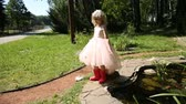 rubber plant : Little girl in rubber boots in a flower garden