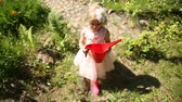pomáhá : A little girl is walking in the garden with a red watering can
