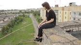 udatnost : Teen girl sitting on the edge of the roof