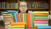 incasso : The girl in glasses in the library hugs books. Stockvideo