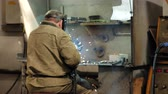 lakatosmunka : Welder in protective mask and overalls welds metal structures in the shop of the factory, metalworking at the factory, welding and metal processing