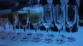 alkoholik : A waiter pours champagne into glasses at a club party. Glasses with champagne on the table are illuminated with different colors of light music. Close-up of glasses