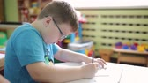 pero : The boy with glasses writes in pencil in a notebook. Pupil in elementary school solves a logical problem. A lesson in elementary school on logic and mathematics. Preschool education. Dostupné videozáznamy