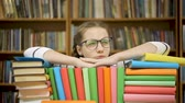 túlhajszolt : Girl takes off glasses after reading a book. A girl lies on books in the library. Stock mozgókép