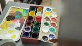 corante : .Open cans of gouache for drawing. Multi-colored paints of the artist. The artist draws yellow paint on a brush with a polytr. Stock Footage