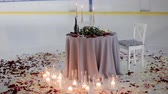 róża : A table for a romantic dinner is decorated with candles and rose petals on ice in the middle of the ice rink of the stadium. Ice rink for lovers Wideo