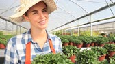 smell : smiling woman in greenhouse with plants Stock Footage