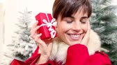 shopping bag sale : Christmas woman opens bag with gift and surprised smiles, with trees in the background