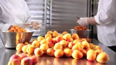 conserva : hands pastry chef cutting apricots, prepare the jam in industrial kitchen worktop.