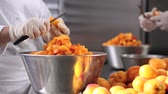 kruvasan : hands pastry chef cutting apricots, prepare the jam in industrial kitchen worktop.