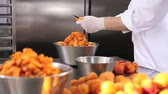 przetwory : hands pastry chef cutting apricots, prepare the jam in industrial kitchen worktop.