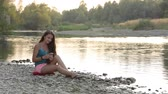 play : girl of European appearance, teenager, a woman with long hair brunette with brown eyes, sitting, running, standing on the river bank near the water, dressed in blue shirt, pink shorts, shoes, black sneakers, a serious or smiling, happy, resting answers th
