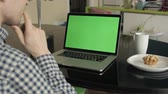 sólido : A man types on a laptop on his desk.  Green screen for your custom screen content. Stock Footage