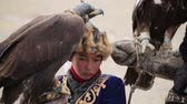 berkut : Bayan-Ulgiy, Mongolia - November 5, 2014: Festival golden eagle hunting. Golden eagle on the hand girl. Girl holding a golden eagle on the hand on the national holiday