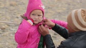 clothe : Bayan-Ulgiy, Mongolia - November 5, 2014: Festival golden eagle hunting. Buttoned jacket daughter. Mother dress daughter Stock Footage