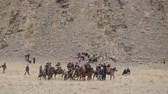 berkut : Bayan-Ulgiy, Mongolia - November 5, 2014: Festival golden eagle hunting. Nomads with eagles riding on horses. Hunters with eagles riding on horseback through mountainous terrain