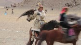 berkut : Bayan-Ulgiy, Mongolia - November 5, 2014: Festival golden eagle hunting. Hunter on horseback with eagle. Mongol with eagle on his arm riding a horse across the steppe