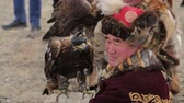 berkut : Bayan-Ulgiy, Mongolia - November 5, 2014: Festival golden eagle hunting. A man with a golden eagle. Hunter with golden eagle waiting for his speech Stock Footage