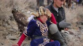 berkut : Bayan-Ulgiy, Mongolia - November 5, 2014: Festival golden eagle hunting. Golden eagle and girl with her father on the mountain. Father with child look at the competition from the slope of the mountain