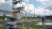 szelep : Oil well for pump out rock-oil for supply. Modern facility with pipe and pump or process area at oil depot or tank farm. Complex for refining and delivery. Outdoors in nature summer. Nobody. Closeup Stock mozgókép