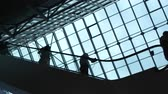 sky : Movement of people on the moving stairway inside the structure of financial company or public place with large glass windows. Metaphor of society economy. Blue color of sky and silhouettes of nation