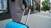 проведение : One sexy lady carry on trendy blue color baggage outdoors close up. Traveler walking at high heels shoe to the hotel for check-in and hold the valise handle. Isolated legs and building at background