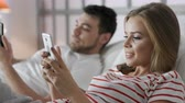 Caucasian modern newlyweds holding smart device in hand indoors. Relation of husband and wife or lovers. Romance of male person and cute female girl. Relaxation with digital social networking everyday