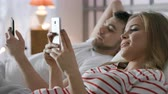 Attractive modern newlyweds holding smart device in hand indoors. Relation of boyfriend and girlfriend or lovers. Romance of male person and cute female girl. Relaxation with digital social networking
