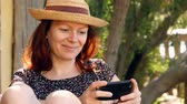 has fun : Woman relaxes in the garden enjoying her smartphone in the sun