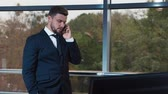 severely : Young businessman talking on the phone at the office window
