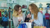 shopping bag sale : Two friends with shopping bags met at the supermarket. Hello, kiss, show each other their purchases Stock Footage