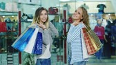 shopping bag sale : Two attractive women posing model looks at the camera with shopping bags. It is against the background of glass showcases in the store Stock Footage