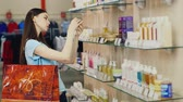 perfume : Attractive brunette chooses cream in a perfume shop Stock Footage
