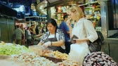 glacé : Barcelona, Spain - June 15, 2016: A woman buys sweets at the famous Boqueria market
