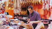 weigher : Barcelona, Spain - June 15, 2016: The man behind the counter of the seller runs a butchers shop. Sales of sausage and ham