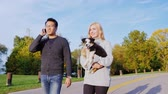 cão de pastor : Young multi-ethnic couple walking in the park. Asian man talking on the phone, near the Caucasian woman walking with a dog in her arms Vídeos