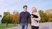 cão de pastor : Happy Together with his beloved dog. Multiethnic couple walking in the park with his dog. Caucasian woman carries a puppy hand, is near an Asian man Vídeos