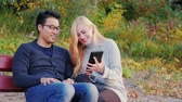 campus : Multinational students communicate in the park, enjoy the tablet. Asian man and Caucasian woman is Stock Footage