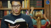 campus : Good looking Asian man in glasses reading a book in the library. In the background a woman looking for a book on the shelves