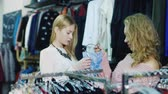 adult : Two young women looking at the underwear in a clothing store. Smiling, talking, visiting goods