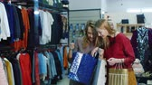 shopping bag sale : Two young women looking at their purchases in bags. Then, out of the store. successful Shopping