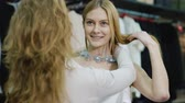 shopping bag sale : Seller consultant helps shoppers to try on jewelry. The department of womens clothing and accessories