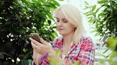 meal : A young blonde woman is resting in a cafe on the summer terrace. Uses a smartphone