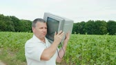 carry out : A serious man is dragging an old unnecessary TV on his shoulder