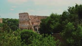 flavian : The famous Colosseum in Rome. In the foreground there are green trees. Summer in Rome Stock Footage