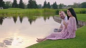 çarpmak : A pregnant woman in a pink dress with her husband. They sit on the grass by the lake