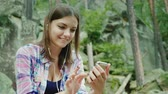 cellular : A young woman tourist uses a smartphone in a hike. Sits resting against the rocks in the mountains Stock Footage