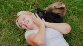 lawn : Woman lies on the lawn, plays with puppies