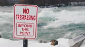 禁止 : A plate with an inscription No trespassing. Dangerous for swimming and for living place. The stormy water of the river flows in the background. Niagara River in front of Niagara Falls 動画素材