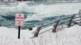 proibir : A sign with a warning about a dangerous place in the river. The stormy water of the Niagara River in front of the waterfall